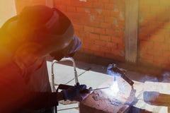 Welder welds on the building site Stock Photos