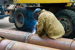 Welder welds pipe segments. Repair and replacement of outdated p Royalty Free Stock Image
