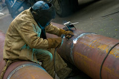 Welder welds pipe segments. Repair and replacement of outdated p Stock Images