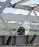 Welder welds the steel bridge construction Stock Photo