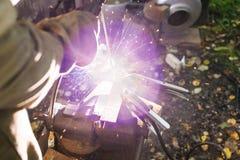 Welder welds steel buckle outdoors Royalty Free Stock Photos