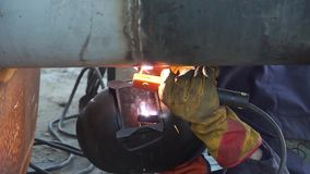 A welder welds technological pipelines with manual arc welding for an oil refinery in Russia. Welded joint. stock footage