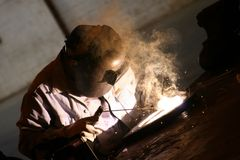 Welder at work. Arc welder at work at his workbench Royalty Free Stock Image