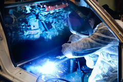 Welder at work. Mechanic with protective mask welding car body Royalty Free Stock Image