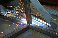 Welder at work. Welder working at metal frame; making sparks Stock Image