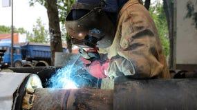 Welder at Work. Welder with protective equipment welding outdoors. Selective focus Stock Image