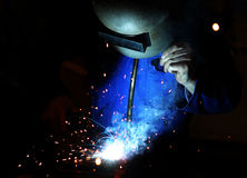 Welder at work. With welding mask and torch Stock Image