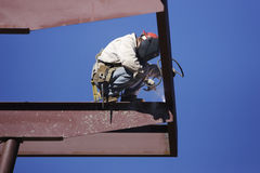 Welder at work. Construction welder welding building girders against a blue sky Stock Image