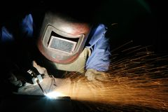 Welder at work. A welder at work, sparks in the air royalty free stock photo