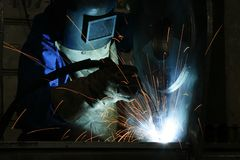 Welder at Work. An industrial worker with welding torch and protective mask Royalty Free Stock Photography