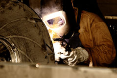 Welder at work. Man is weldind a big place of steel Royalty Free Stock Photo
