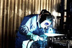Welder at work. Man is weldind a big place of steel Royalty Free Stock Photos