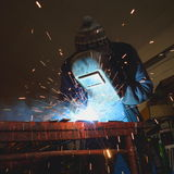 Welder at work. Arc welder wearing protective clothes at work Stock Image