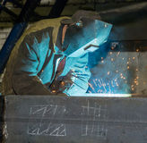 Welder. Welder at work in the blinding light of bright splashes of red-hot metal Stock Photo