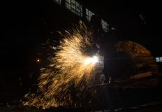 Welder at work in a factory. Welder working in a steel factory. The welding of the metal form spectacular trails of light Stock Photo