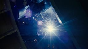 Welder at work in metal industry. Close up of welding. Manufacture of trucks. Worker welding metal stock video
