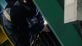 Welder at work in metal industry. Close up of welding. Manufacture of trucks. Worker welding metal stock video footage
