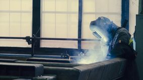 Welder at work in metal industry. Manufacture of trucks. Worker welding metal stock video