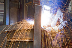 Welder at work. A metal welder at work wearing a mask with sparks flying Stock Photos