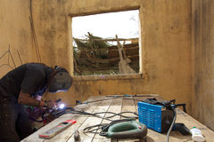 Welder at work in old house in Africa Stock Image