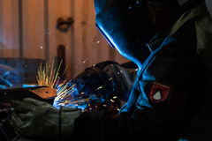 Welder at work. Welder in protective suit and mask at work in profile Stock Photo