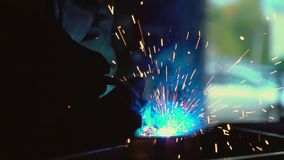 Welder at work. Sparks from welding. Bright sparks from welding against a dark background.. stock footage