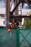 Welder at work. Unrecognizable welder at work at the construction site surrounded by green fence Stock Photography