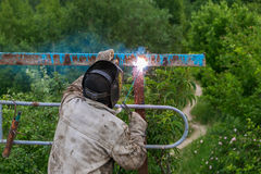Welder at work. Welder cooks metal grate on the ground blowtorch on the ground in special clothes and mask welder. Welder at work. Welder cooks metal grate on Stock Photo