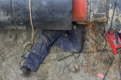 Welder worker grinding the weld in trench under pipeline. After grinding, a second exterior weld is applied over the first weld Royalty Free Stock Images