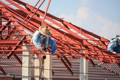 Welder workers installing steel frame structure of the house. Construction welder workers installing steel frame structure of the house roof at building royalty free stock photography