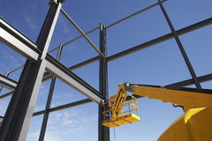 Welder Working From Cherry Picker. On steel framing structure stock photos
