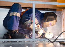 Welder working in cramped conditions. In an uncomfortable position while lying on the floor royalty free stock photos