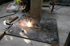 Welder working with electrode at arc welding in construction sit. E Stock Photo