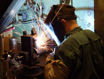 A welder working at the factory. Welder in overalls and a protective mask works in a factory Royalty Free Stock Images