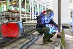 Welder is working at the factory and welding a metal construction.  Stock Photography