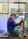 Welder is working at the factory and welding a metal construction.  Royalty Free Stock Photos