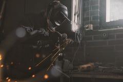 Welder working in garage stock images