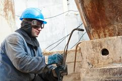 Welder working with gas torch. Manual worker in protective work wear welding by gas torch royalty free stock photo