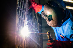 Welder working in industrial factory. Welder working in an industrial setting manufacturing steel equipment Royalty Free Stock Photos