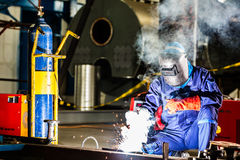 Welder working in industrial factory. Welder working in an industrial setting manufacturing steel equipment Royalty Free Stock Photography