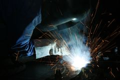 Welder working with metal. A welder wearing a mask and working with metal Royalty Free Stock Photography