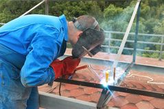 Welder working with metal construction. Man at work: welder worker on constructiion site  working with metal construction Stock Photo