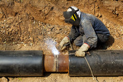 Welder working   pipeline. The welder in protection to a mask working over pipeline connection Stock Images