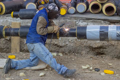 Welder working on pipeline construction. Pipe is supported by crane. Pipe is tack welded Royalty Free Stock Image