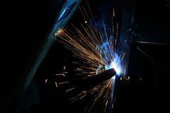 A welder working with sparks flying around Royalty Free Stock Photos