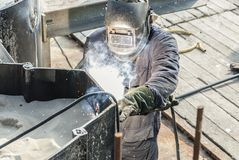 Welder at a workside. Welder working on a steel construction with protected clothing with a weld tool in his hand Stock Photography