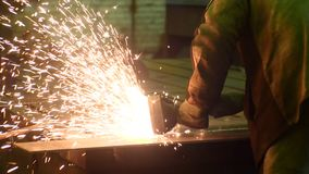 Welder works circular saw, cuts metal. Flies of spark from hot metal. In slow motion stock video