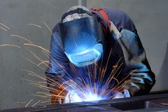 Welder works in an industrial company - production of steel comp. Onents stock photography