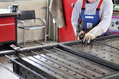Welder works in a metal construction company. Detail photo - man built a metal door Royalty Free Stock Images
