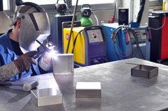 Welder works in a metal construction company. Detail photo with workmen and interieur Stock Photos